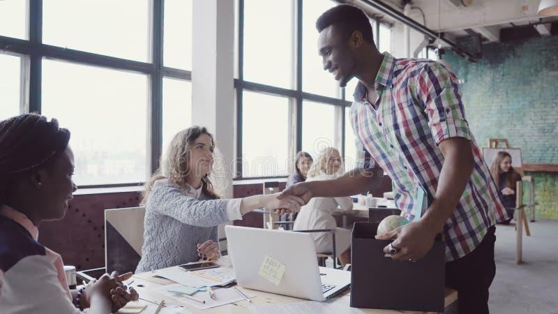 Afrikaanse mens die onlangs op bedrijf in gekomen nieuw kantoor wordt ingehuurd De mannelijke greepdoos met persoonlijke bezittin stock foto's
