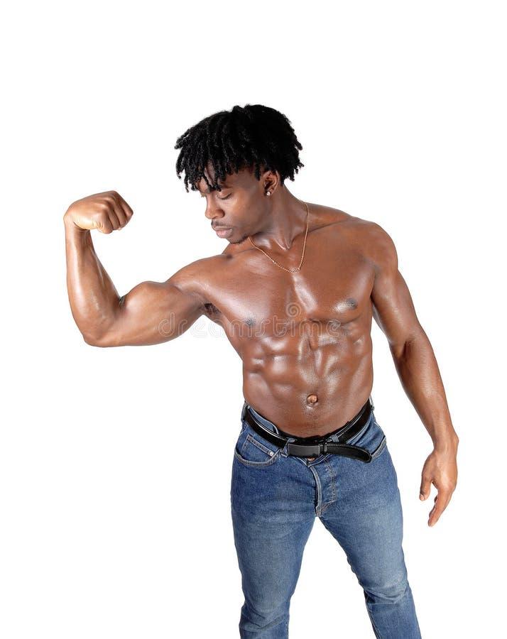 Afrikaanse mens die zijn bicepsen buigen en op het kijken stock afbeelding