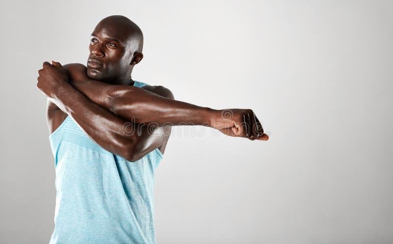 Afrikaanse mens met spierbouwstijl het uitrekken zich wapens royalty-vrije stock foto