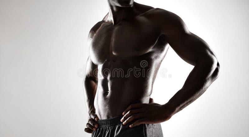 Afrikaanse mens met spierlichaam op grijze achtergrond royalty-vrije stock foto's