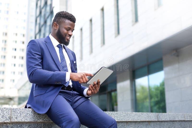Afrikaanse millennial gebruikende technologie als bekwame manier te werken stock foto