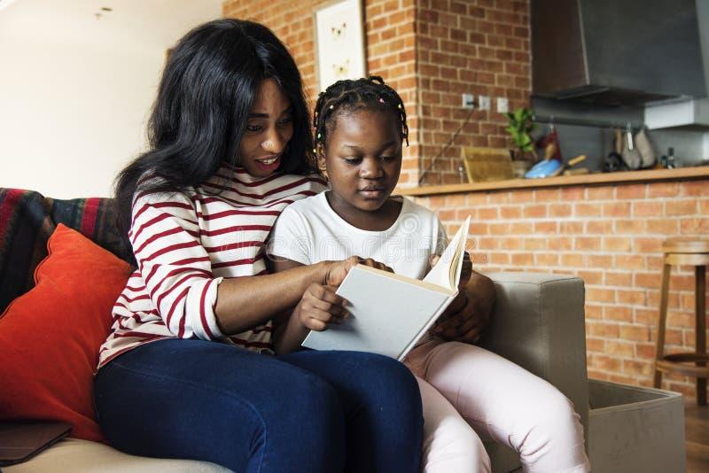 Afrikaanse moeder die haar dochter in het doen van haar thuiswerk helpen stock afbeeldingen