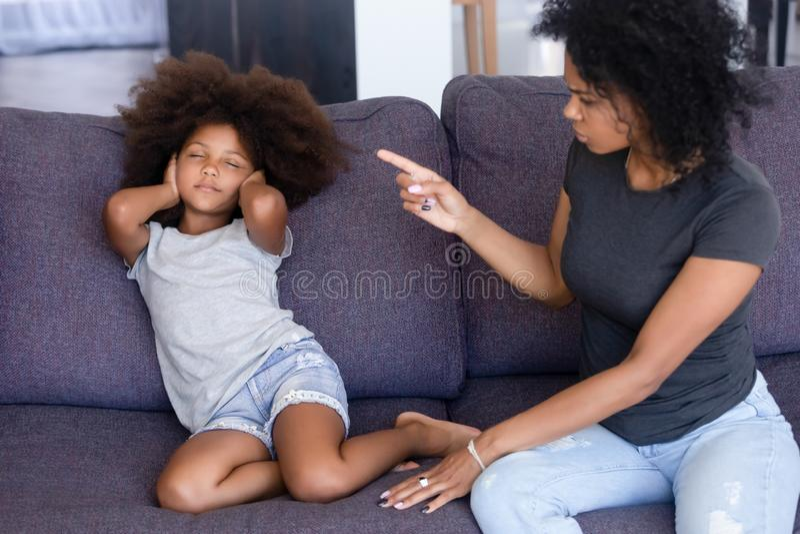 Afrikaanse moeder die weinig dochterzitting op laag thuis berispen stock foto