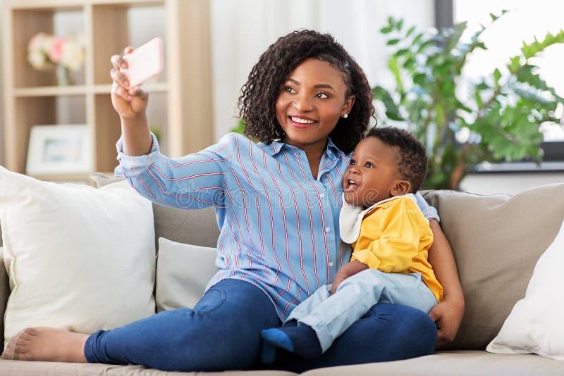 Afrikaanse moeder met babyzoon het nemen selfie thuis stock afbeelding