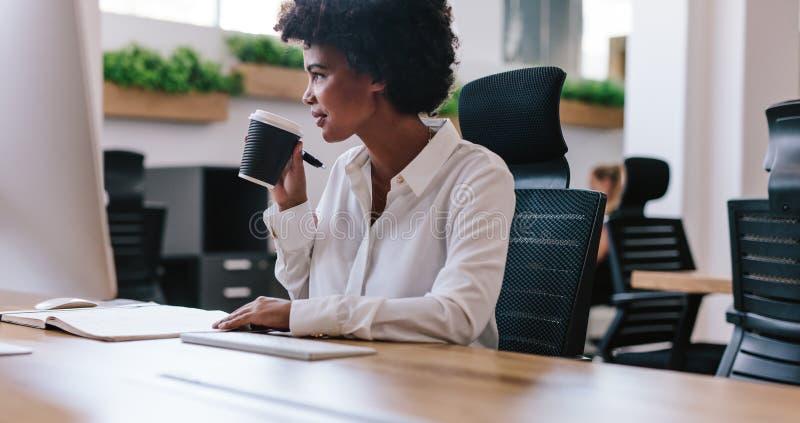 Afrikaanse onderneemster die koffie hebben bij haar bureau royalty-vrije stock afbeelding