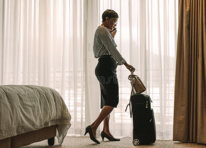Afrikaanse onderneemster die op telefoon van hotelruimte spreken royalty-vrije stock afbeelding