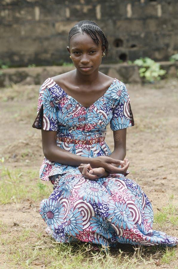 Afrikaanse schoonheidszitting die in openlucht onder de zon stellen stock fotografie