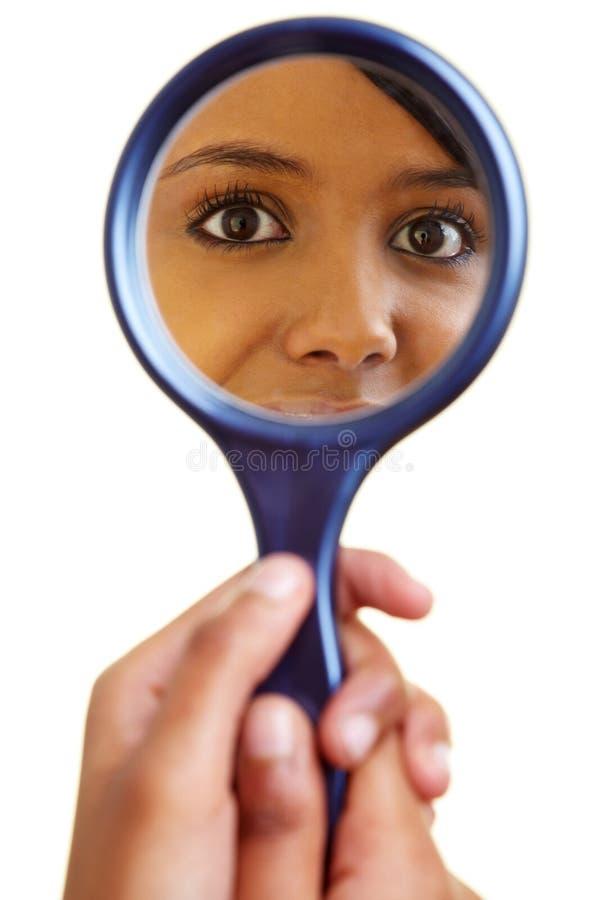 Afrikaanse vrouw die een spiegel onderzoekt stock foto