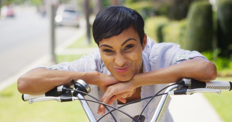 Afrikaanse vrouw die en op fietssturen glimlachen leunen stock afbeelding