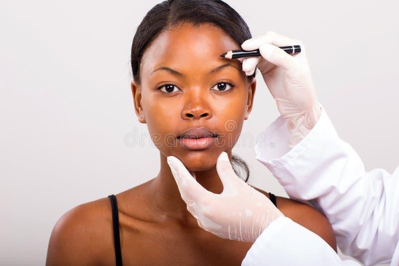 Afrikaanse vrouw die gezicht merken stock fotografie
