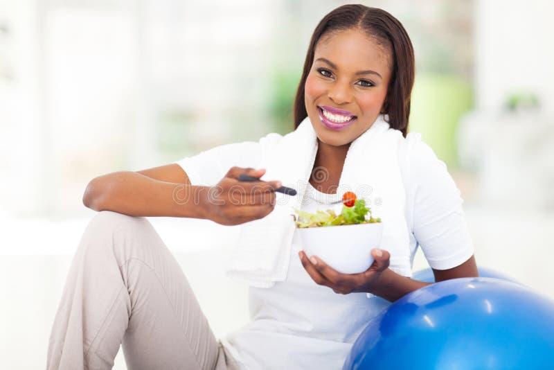 Afrikaanse vrouw die groente eten stock afbeelding