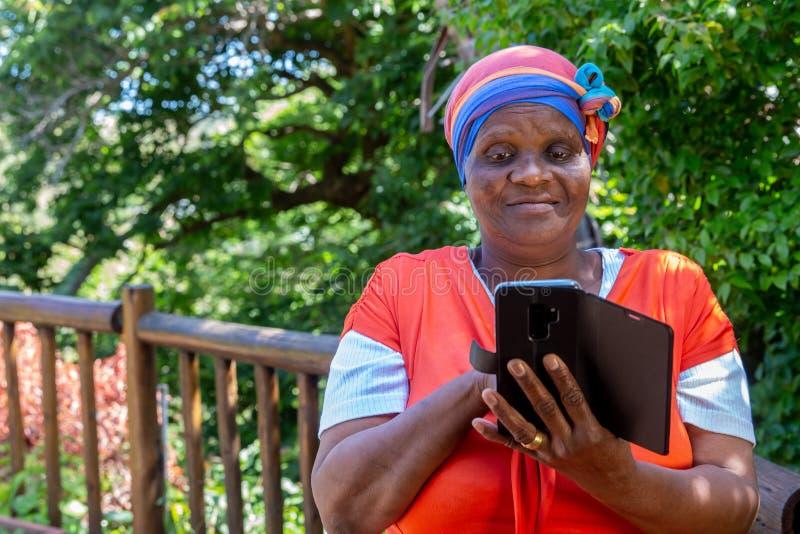 Afrikaanse vrouw die haar cellphone bekijken stock afbeelding