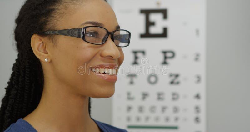 Afrikaanse vrouw die op haar nieuwe glazen proberen stock afbeeldingen