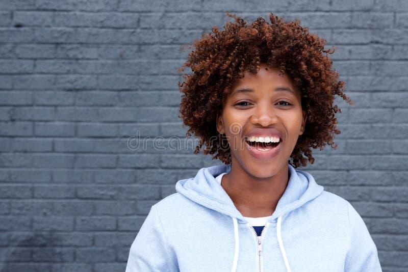 Afrikaanse vrouw die tegen grijze bakstenen muur lachen stock fotografie