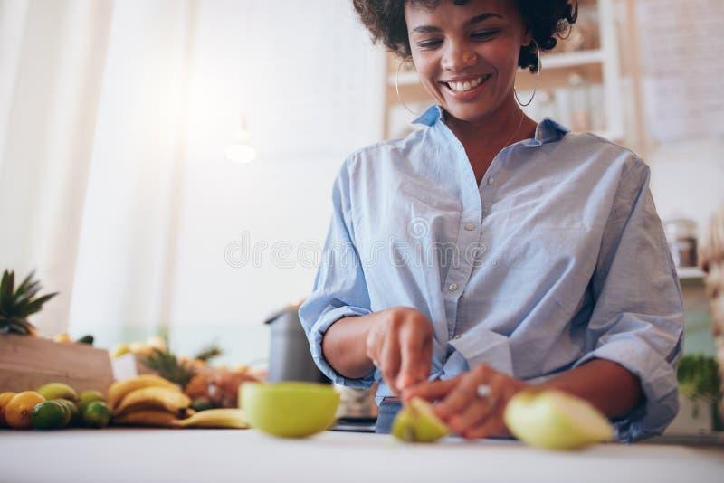 Afrikaanse vrouw die vers vruchtensap voorbereiden stock afbeelding
