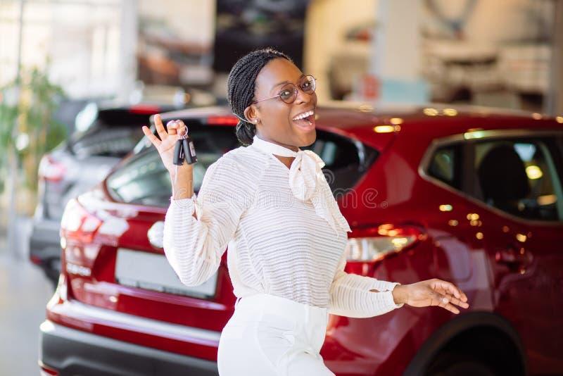Afrikaanse vrouw met haar nieuwe auto die sleutel tonen royalty-vrije stock foto