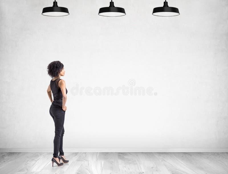 Afrikaanse vrouw met handen op taille dichtbij blinde muur stock afbeeldingen