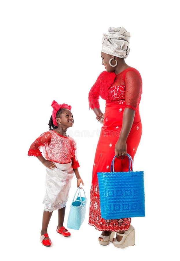 Afrikaanse vrouw met meisje in traditionele kleding met totalisatorzakken stock afbeeldingen
