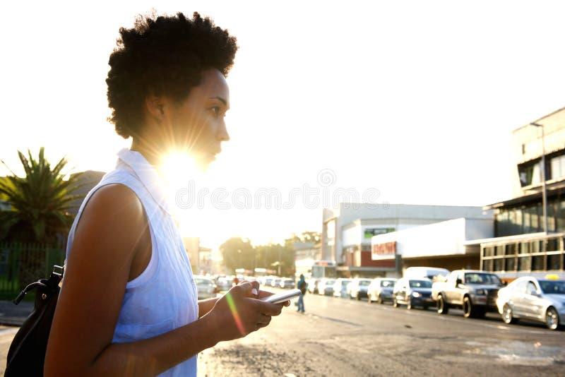 Afrikaanse vrouw met mobiele telefoon op de stadsstraat stock foto's