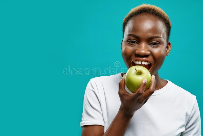 Afrikaanse vrouw met perfecte witte tanden die groene appel bijten stock foto's