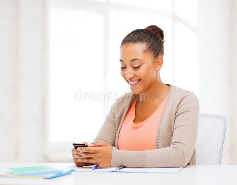 Afrikaanse vrouw met smartphone in bureau stock foto
