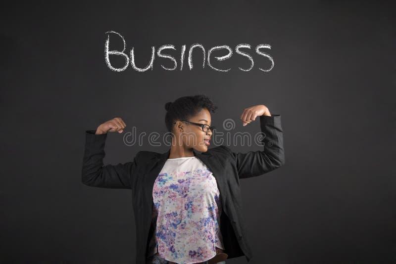 Afrikaanse vrouw met sterke wapens voor zaken op bordachtergrond stock foto's