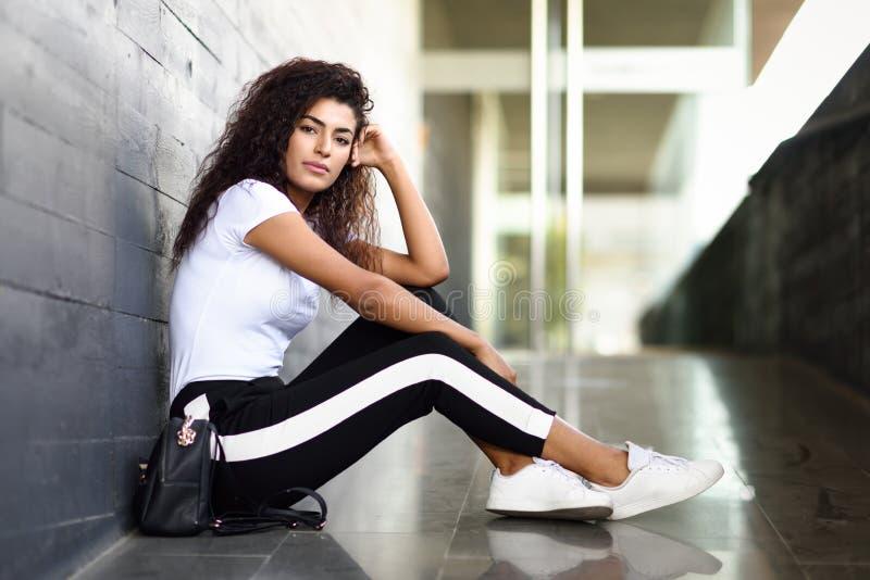 Afrikaanse vrouw met zwarte krullende kapselzitting op stedelijke vloer royalty-vrije stock afbeelding