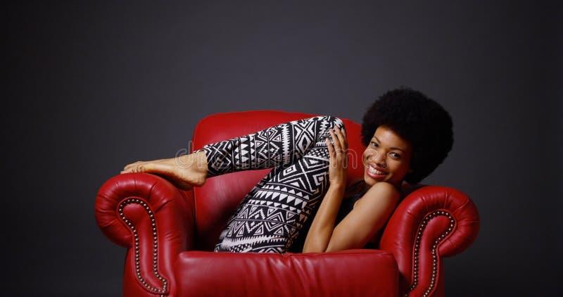 Afrikaanse vrouw in rode de stoel van het leerwapen het schoppen benen speels stock afbeelding