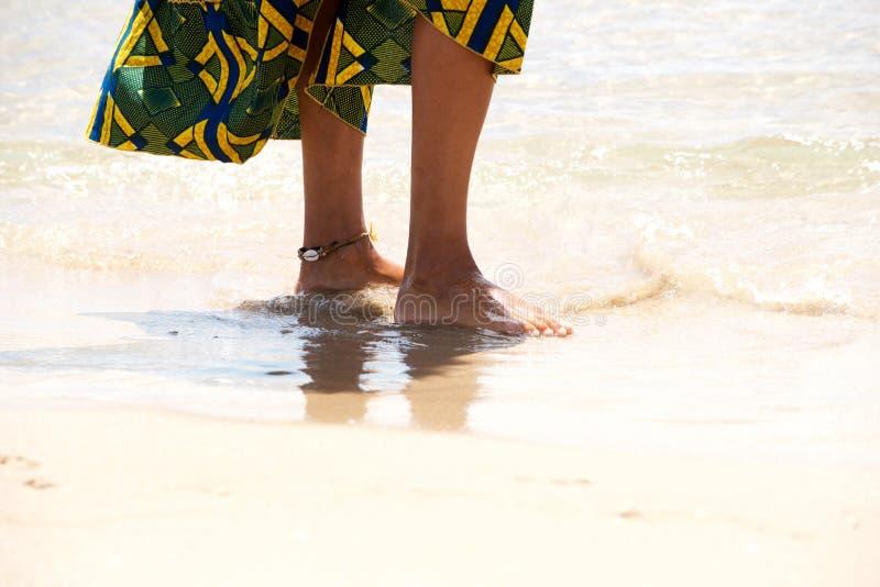 Afrikaanse vrouwelijke voeten die zich op de overzeese kust bevinden stock fotografie