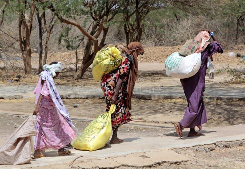 Afrikaanse vrouwen die de hulp dragen die zij aan hun huizen hebben ontvangen royalty-vrije stock fotografie