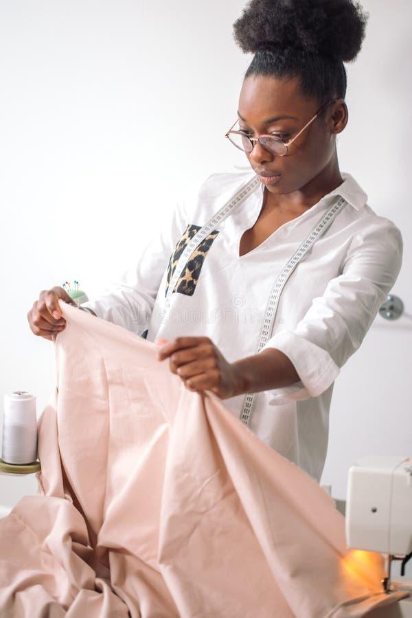 Afrikaanse vrouwennaaister die roze stoffen bekijken en zich in workshop bevinden royalty-vrije stock foto