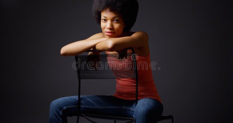 Afrikaanse vrouwenzitting terloops met wapens over rug van stoel stock fotografie