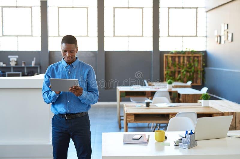Afrikaanse zakenman die met een digitale tablet in een bureau werken stock foto's