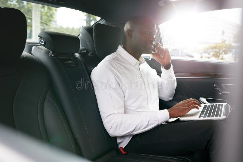 Afrikaanse zakenman die tijdens het reizen naar bureau in een auto werken stock foto