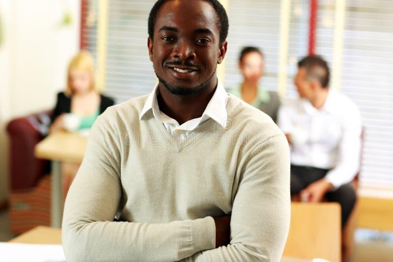 Afrikaanse zakenman die zich voor collega's bevinden stock afbeeldingen