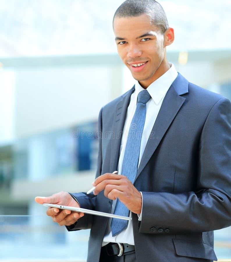 Afrikaanse zakenman met tabletcomputer in bureau stock afbeelding