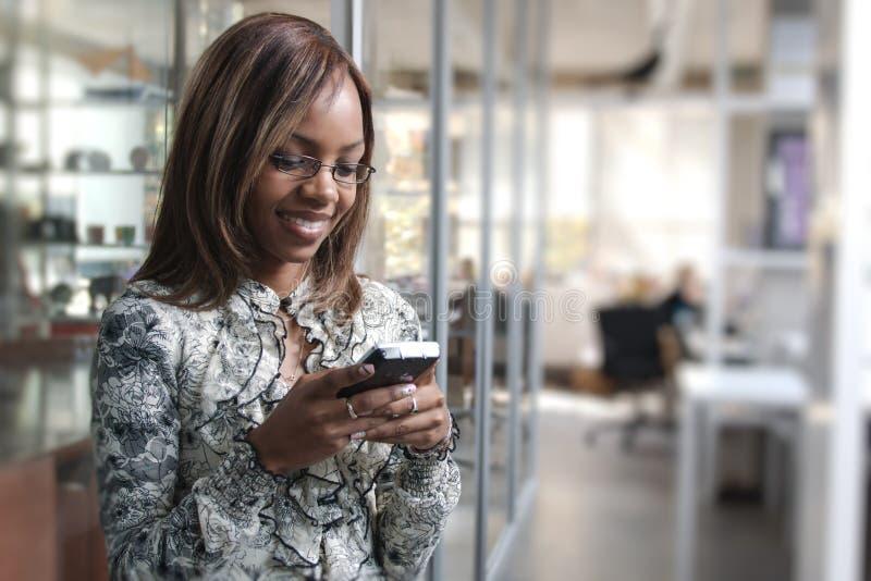 Afrikaanse of zwarte Amerikaanse vrouw die of op mobiele cellphonetelefoon roepen texting in bureau