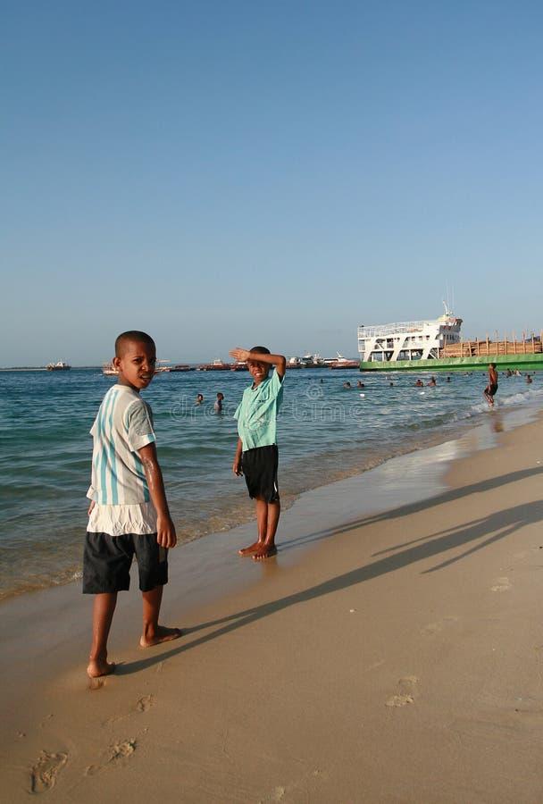 Afrikan för två pojkar som promenerar den sandiga stranden för shoreline, Zanzibar arkivfoto