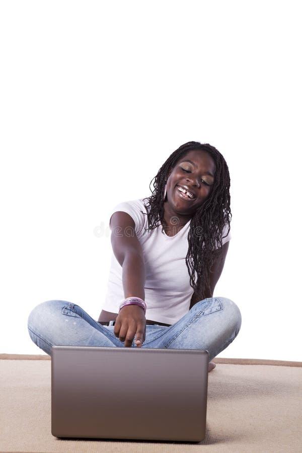 afrikan henne fungerande barn för bärbar datorkvinna arkivfoton