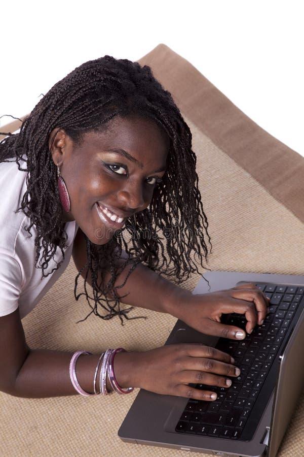 afrikan henne fungerande barn för bärbar datorkvinna royaltyfri fotografi