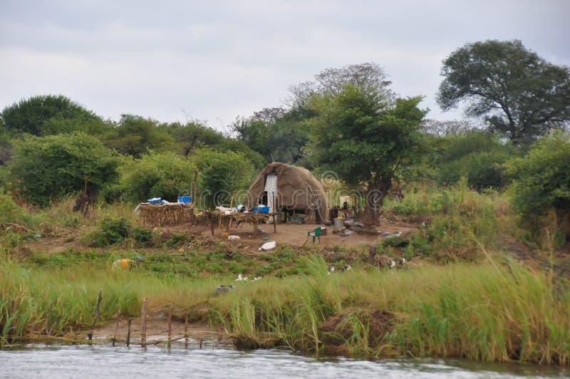 Afrikan som förlägga i barack bredvid floden arkivfoton