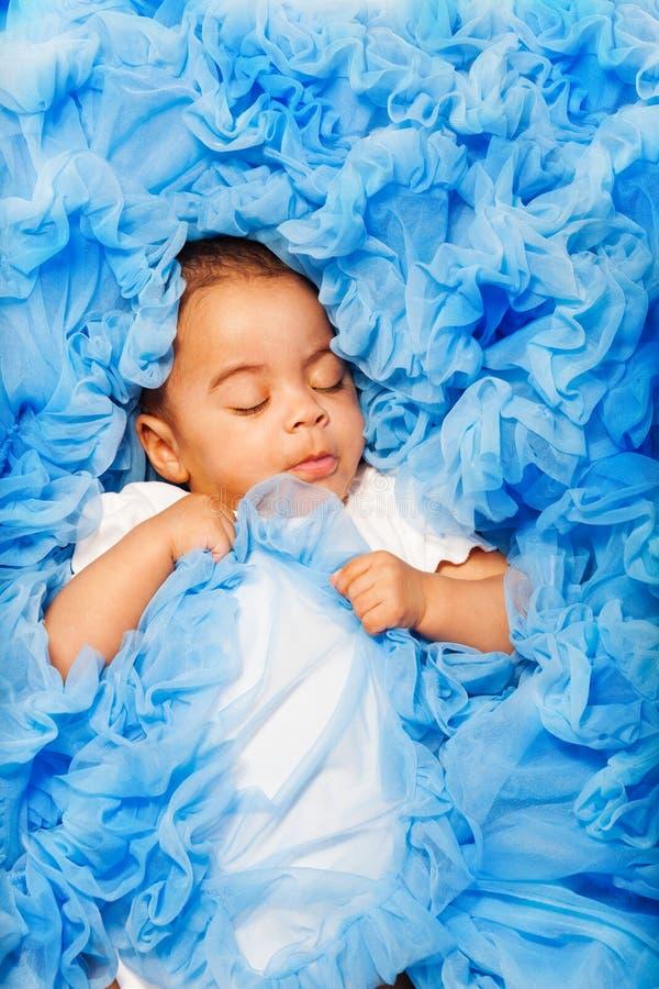 Afrikanen behandla som ett barn att lägga och att sova på den blåa torkduken royaltyfri fotografi