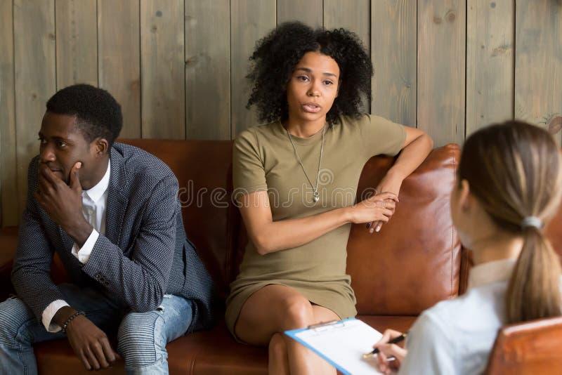 Afrikanen frustrerade frun som talar till psykologen, familjförbindelse royaltyfri fotografi