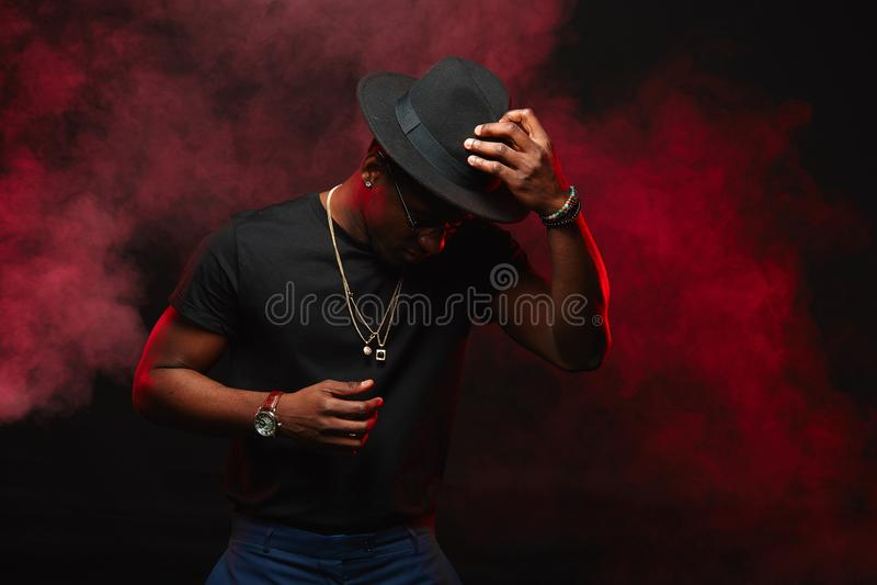 Afrikaner DJ oder Jazzmusiker im Hut und im schwarzen T-Shirt auf dunklem Hintergrund stockfotografie