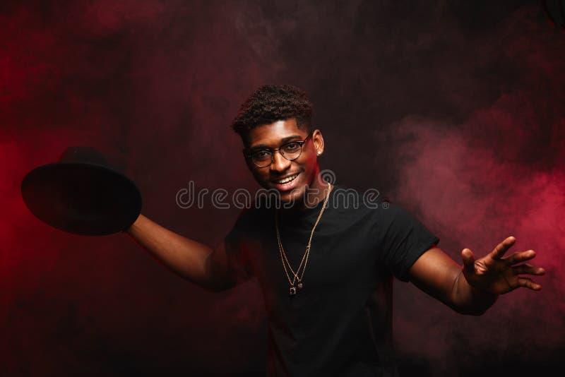 Afrikaner DJ oder Jazzmusiker im kreativen Hut l?chelnd im schwarzen T-Shirt auf Dunkelheit stockfotografie