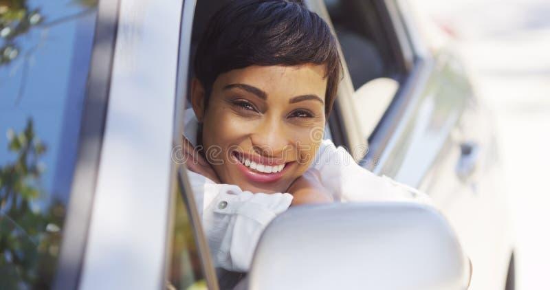 Afrikanerin, die aus Autofenster heraus lächelt und schaut lizenzfreie stockfotos