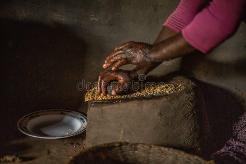Afrikanerin, die Erdnussbutter in ihrer Haupthütte macht stockbilder