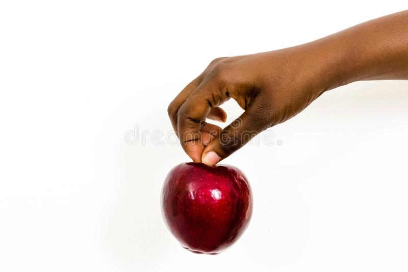 Afrikanerin, die köstlichen roten Apfel durch den Stiel lokalisiert auf einem weißen Hintergrund hält stockfotos