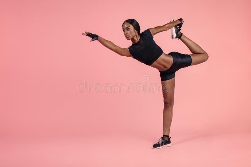 Afrikanerin, die Natarajasana-Yogahaltung übt lizenzfreie stockfotos