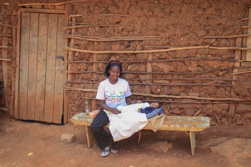Afrikanerin in einem weißen T-Shirt, das ein Baby in ihren Armen hält und auf einer Bank nahe einer Lehmhütte sitzt lizenzfreie stockfotos